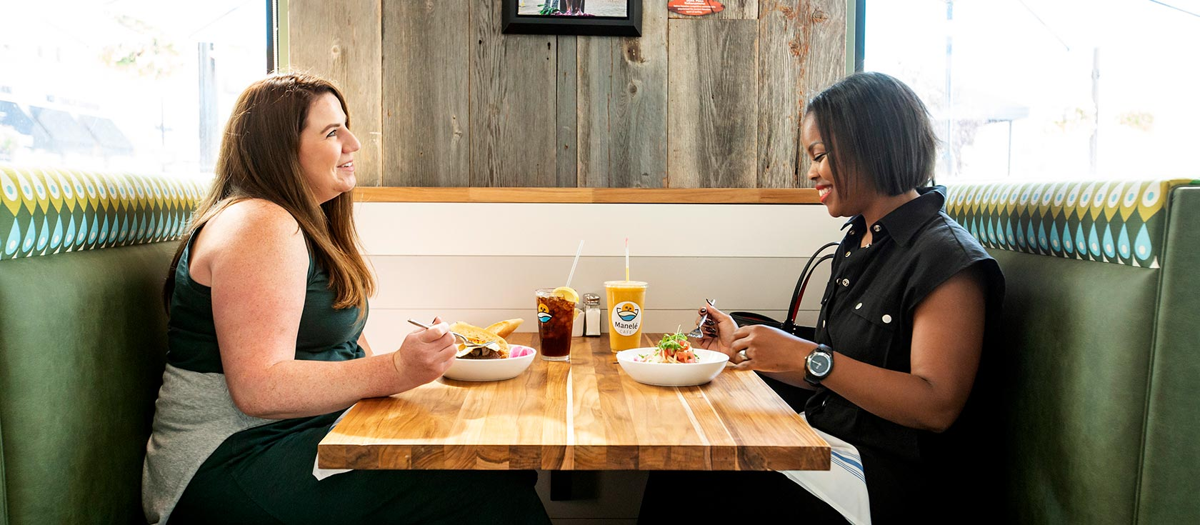 Two young women seated in booth enjoying lunch