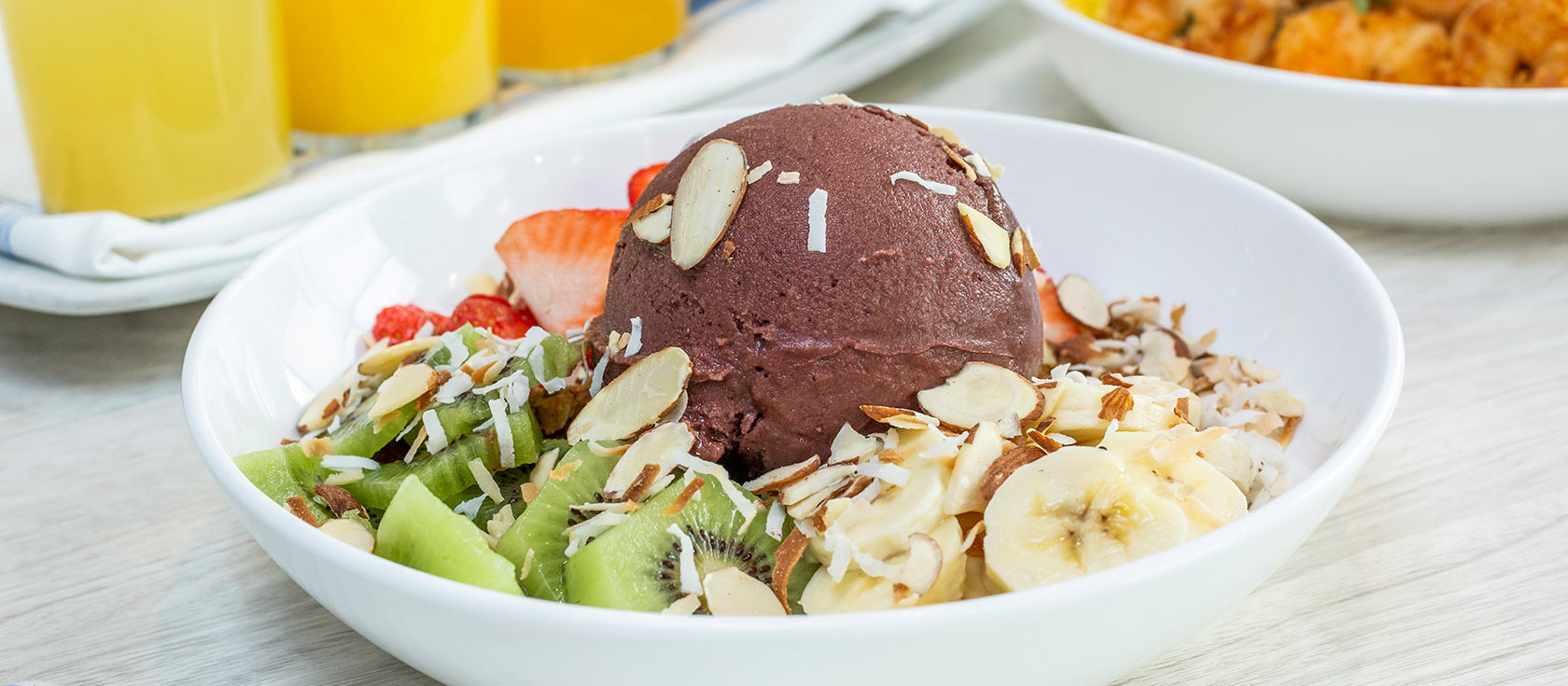 Manele acas bowl with sliced bananas and strawberries